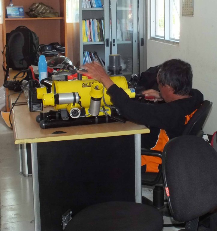Salah satu tim sar lagi membersihkan alat robot dalam air